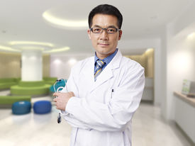 picture of hospital gown  - portrait of a male asian doctor in hospital lobby - JPG