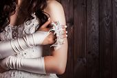 stock photo of garter  - bride holding a garter against wooden background - JPG