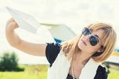 picture of propeller plane  - beautiful woman holding paper plane against real plane - JPG