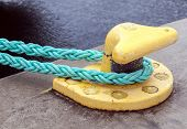 stock photo of bollard  - Horizontally oriented picture of port pier with yellow mooring bollard and green ropes - JPG
