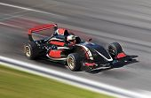 stock photo of race track  - Formula one race car on speed track with motion blur - JPG
