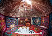 picture of yurt  - Ethnic nomadic house yurt interior with table of national food at Nauryz celebration - JPG