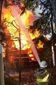 image of fireman  - Fireman use water on house in fire