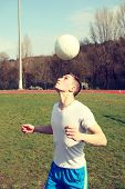 stock photo of juggling  - Young man juggles ball with his head in a stadium - JPG