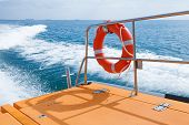 stock photo of life-boat  - Red lifebuoy hanging on railings of fast safety rescue boat - JPG