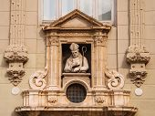 stock photo of building relief  - Sculpture of the Catholic priest is decorated  old building in Valencia - JPG