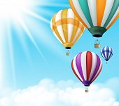 stock photo of  realistic  - Realistic Colorful Hot Air Balloons Background Flying in the Blue Sky with Sun Rays and Clouds with Space for Writings - JPG