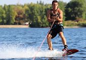 stock photo of watersports  - Happy handsome man wakesurfing in a lake and pulled by a boat - JPG
