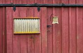 stock photo of red barn  - Weathered Red Barn Door with Iron Fixtures and copy space - JPG