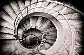 picture of stairway  - Walking woman in center of spiral stairs in black and white with light center and burned edges - JPG