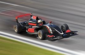 picture of race track  - Formula one race car on speed track with motion blur - JPG