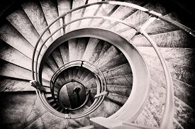 pic of stairway  - Walking woman in center of spiral stairs in black and white with light center and burned edges - JPG