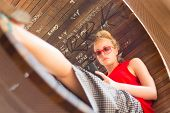 pic of casual wear  - Casually dressed young cheerful lady wearing red sunglasses playing carelessly with her android smarthphone browsing trough social networks relaxing on  contemporary circular bench in city park - JPG
