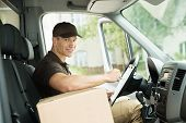 pic of moving van  - Young Happy Delivery Man With Cardboard Box Checking List In Van - JPG