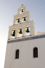 picture of blue-bell  - Ropes attached to the bells of a bell tower in front of the light blue sky of a church in Santorini Greece