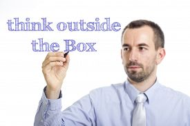 foto of thinking outside box  - Think outside the Box Young businessman writing blue text on transparent surface - JPG