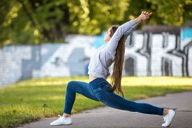 picture of virabhadrasana  - Profile of beautiful sporty young woman working out on city street doing warming up lunge exercise virabhadrasana 1 warrior 1 sun salutation complex full length - JPG