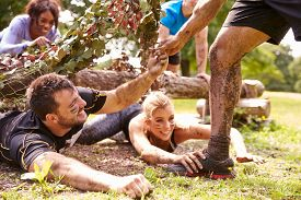 foto of crawl  - Assault course competitor helping others crawl under nets - JPG