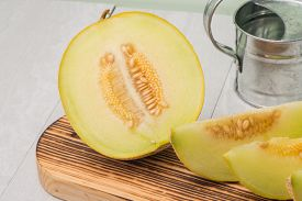 stock photo of honeydew melon  - Juicy honeydew melon on a wooden table background - JPG