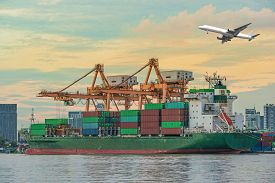 stock photo of shipyard  - Container Cargo freight ship with working crane loading bridge in shipyard at dusk for Logistic Import Export background - JPG