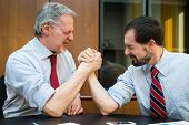 Business people doing arm wrestling in their office. Shallow depth of field, focus on the man on the poster