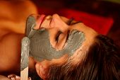 Mud facial mask of woman in spa salon. Back massage with clay full face . Girl on Luxary interior wi poster