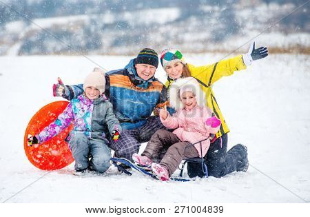 poster of Active happy family smiling and laughing while playing outdoors during winter holidays. Winter fun o