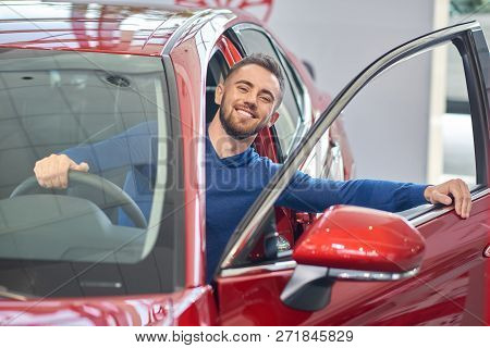 poster of Young Handsome Man Almost Sitting In Red Car And Closing Front Door. Brunette Client In Car Salon Sm