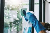 Husband Housekeeping And Cleaning Concept, Happy Young Man Wiping Dust Using A Spray And A Duster Wh poster