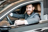 Portrait Of An Elegant Businessman With Provocative Emotion On The Driver Seat In The Luxury Car At  poster