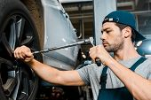 Focused Male Auto Mechanic In Working Overall Working With Wheel Wrench At Auto Mechanic Shop poster