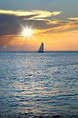 Colorful seascape image with shiny sea and sailboat over cloudy sky and sun during sunset in Cozumel poster