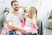 Adorable Little Daughter In Pink Tutu Skirt Applying Makeup To Happy Father poster