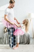 Side View Of Happy Father And Little Daughter In Pink Tutu Skirts Holding Hands And Dancing At Home poster
