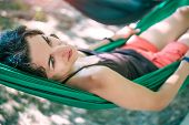 The Girl Is In A Hammock. Woman Resting Lying In A Green Fabric Hammock. Rest In The Woods. poster