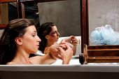 Woman relaxing in bathtub with mirror image of her with bruises on her face, a conceptual shoot of domestic abuse often hidden from public poster