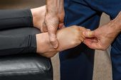 Chiropractor Pulls On The Toe Of A Girl To Adjust Her Foot.  He Muscle Tests The Foot In Order To Es poster