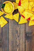 Snack For Party. Mexican Nachos Near Guacamole Sause On Dark Wooden Background Top View Copy Space poster
