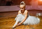 A Portrait Of A Little Sweet Ballerina In A White Tutu Sitting On The Floor And Tying Pointe Shoe In poster