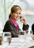 Happy businesswoman talking on cell phone in conference room