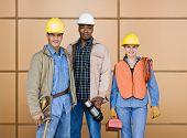 Постер, плакат: Многоэтнического строительных рабочих позируя в hard hats с инструментами