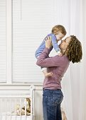 Devoted mother lifting son from crib in bedroom