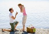 stock photo of propose  - Boyfriend proposing to girlfriend near stream - JPG