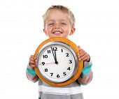 stock photo of nursery school child  - Smiling nursery school child holding a clock - JPG