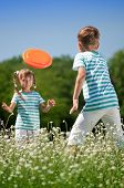 foto of frisbee  - Happy boy and little girl playing frisbee on a meadow in a sunny day - JPG