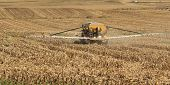 stock photo of spreader  - Vehicle spreading fertilizer on a farm field of corn stubble - JPG