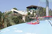 image of inflatable slide  - Girl is sitting on wet bubble game pool in water park Rhodes - JPG