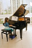 pic of musical instruments  - little girl playing the grand piano at home - JPG