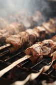 stock photo of brazier  - Fresh meat on a steel skewer in a smoke at brazier - JPG