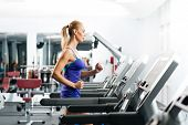 image of treadmill  - attractive young woman runs on a treadmill - JPG